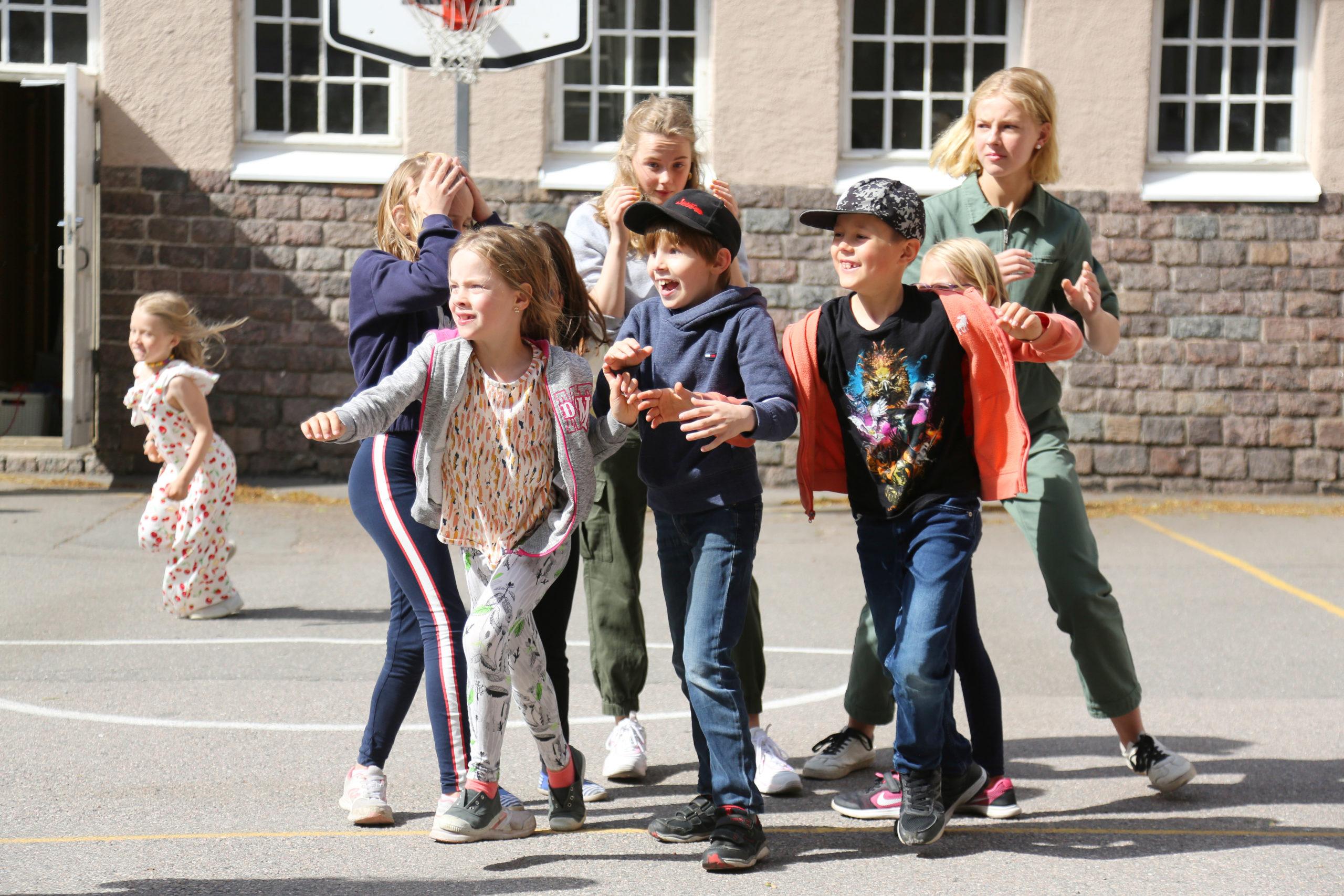 En grupp med barn leker på skolgården