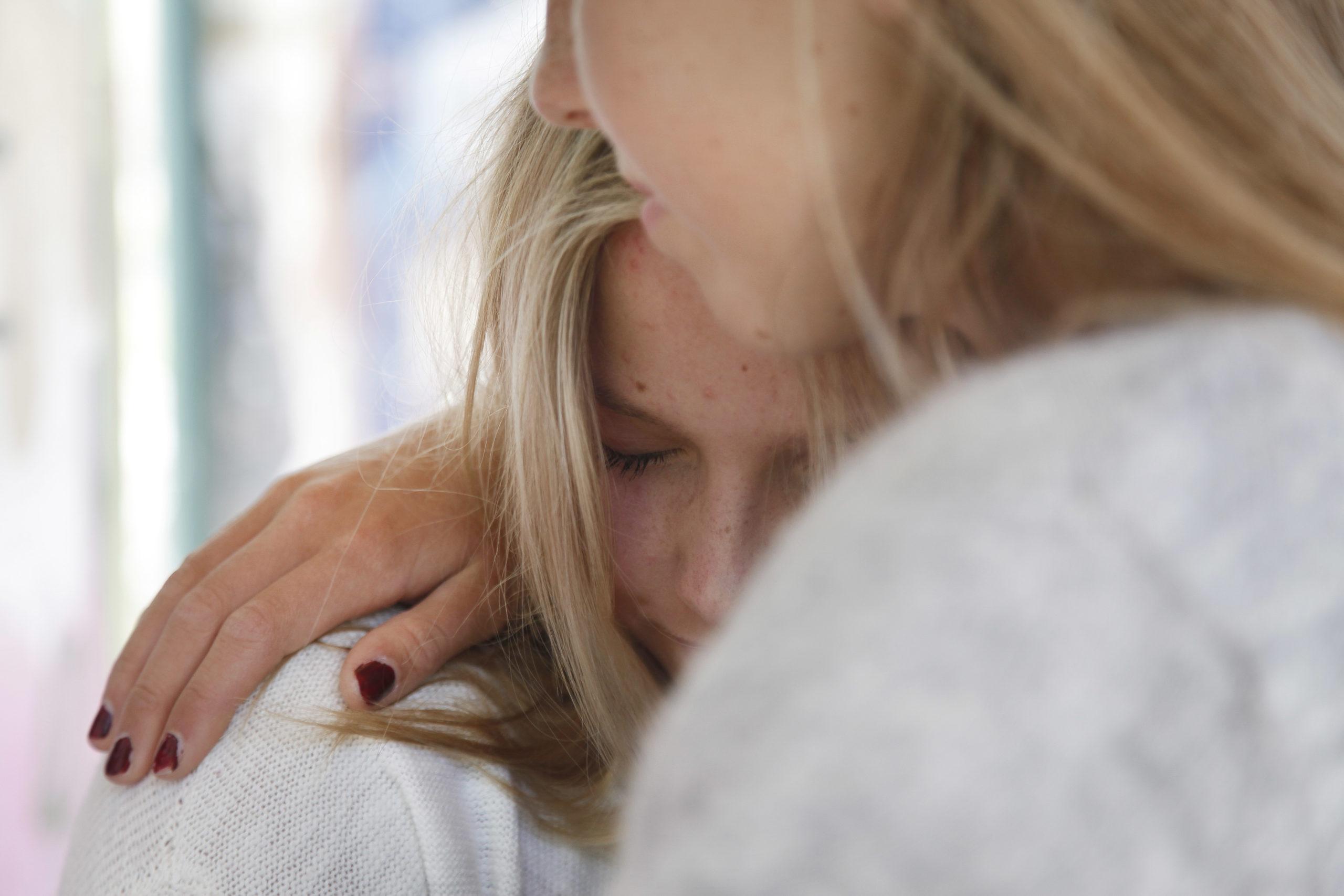 Aikuinen halaa nuorta