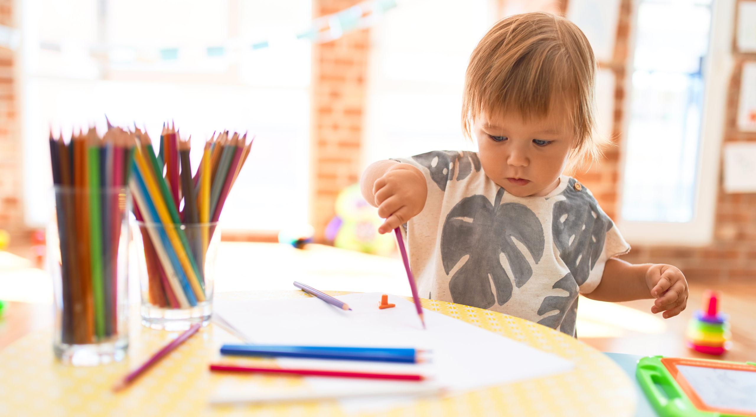 Ett litet barn ritar med färgpenna
