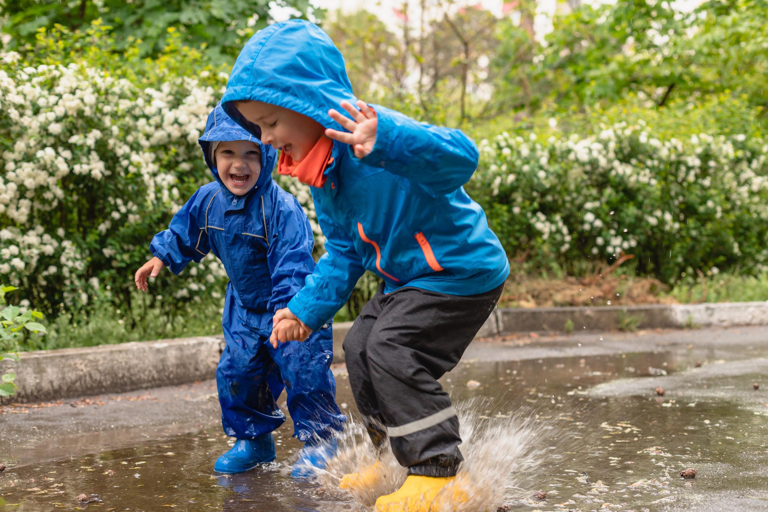 Barn i gallonkläder hoppar i en vattenpöl